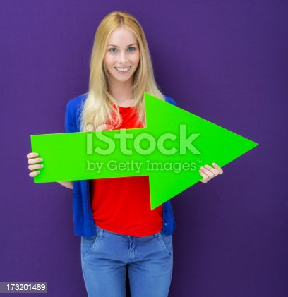 168589045istockphoto Young woman pointing with a green arrow 173201469