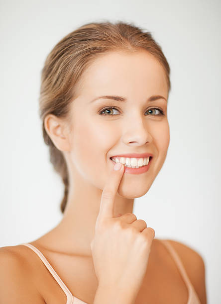 young woman pointing with one finger to her white teeth - straight stock photos and pictures