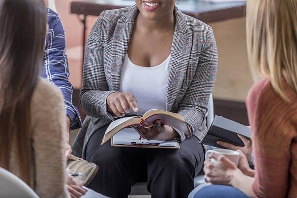 young woman points to a scripture verse during bible study - geführtes lesen stock-fotos und bilder