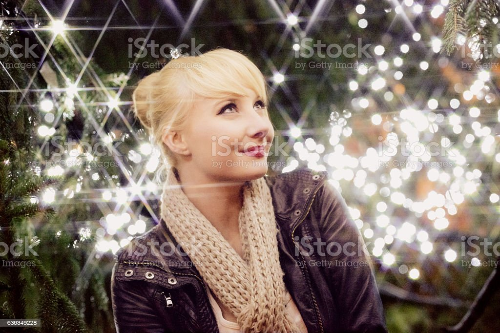 Young Woman Portrait against Glowing Christmas Tree stock photo