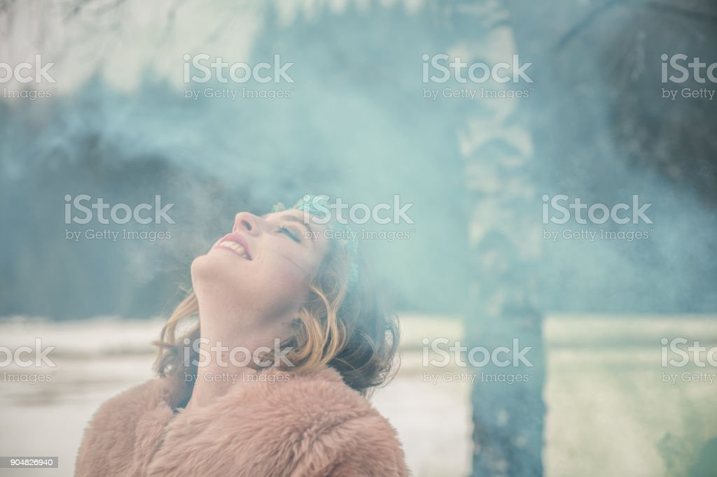 Young woman portrait outdoors with green smoke bomb stock photo