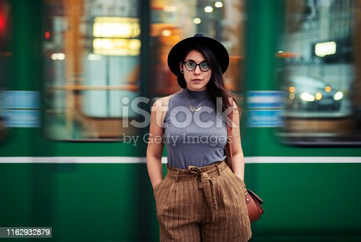 Portrait of young beautiful Latino woman standing on focus in front of blurred green tramway on background at lowlight.