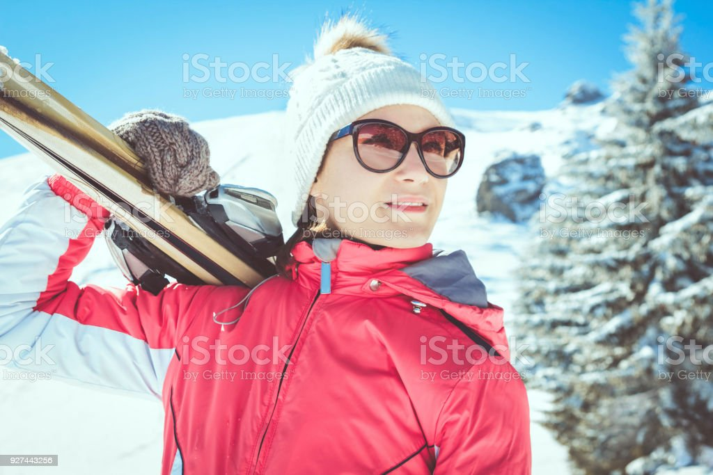 b45cb2c51c0 Young woman portrait skier holding skis standing in winter mountains royalty -free stock photo