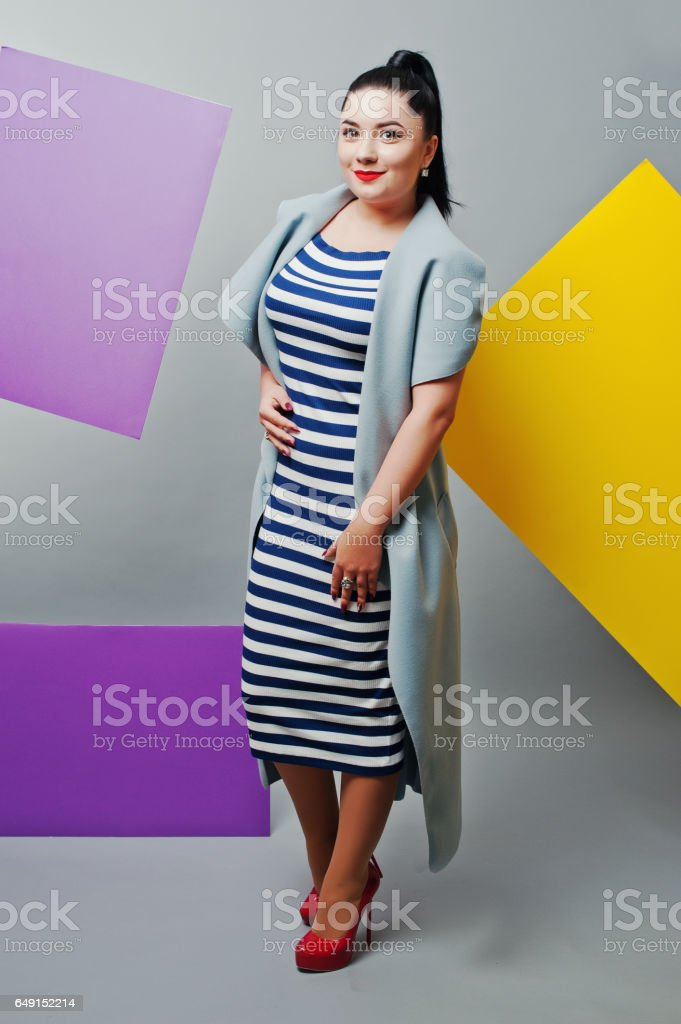 Young woman portrait with blank yellow and purple banner, board on gray isolated. stock photo
