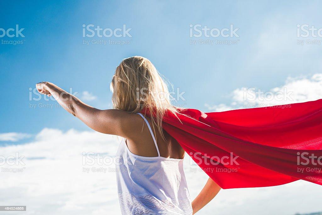 Young woman posing as superhero over blue sky stock photo