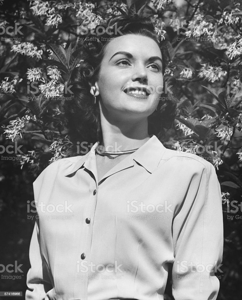 Young woman posing by blooming tree, (B&W), (Close-up), (Portrait), (Low angle view) stock photo