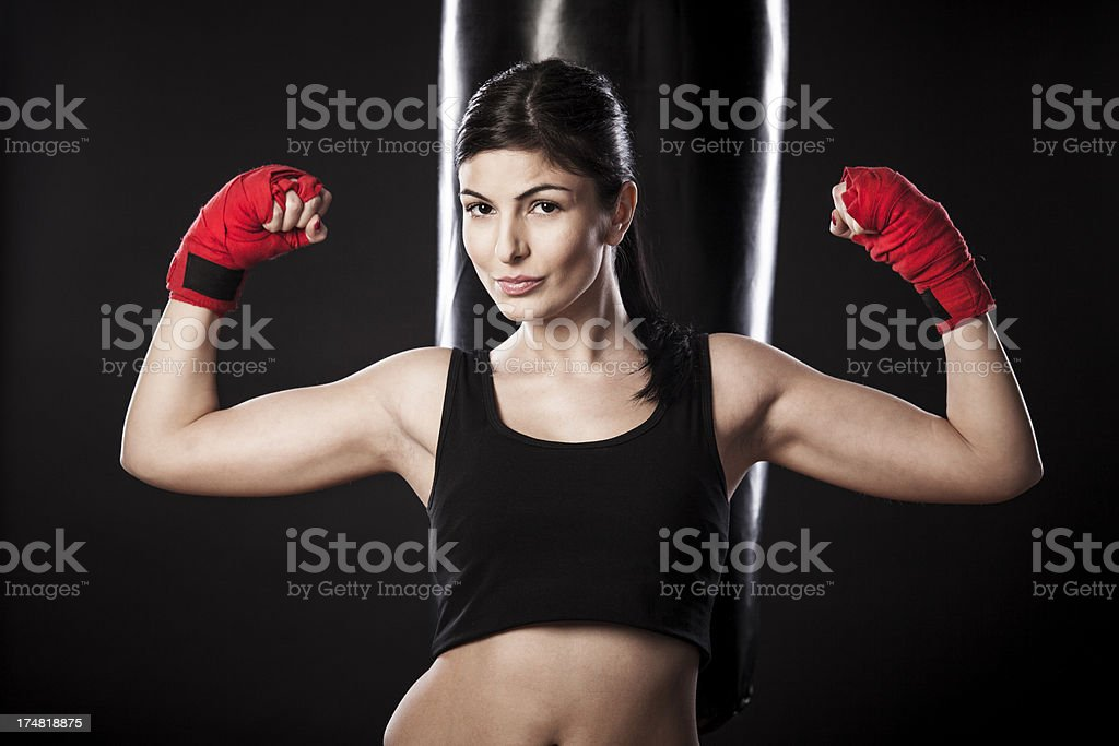 Young woman posing in front of a punching bag royalty-free stock photo