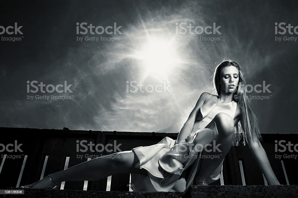 Young Woman Posing Near Fence with Dramatic Sky, Toned royalty-free stock photo