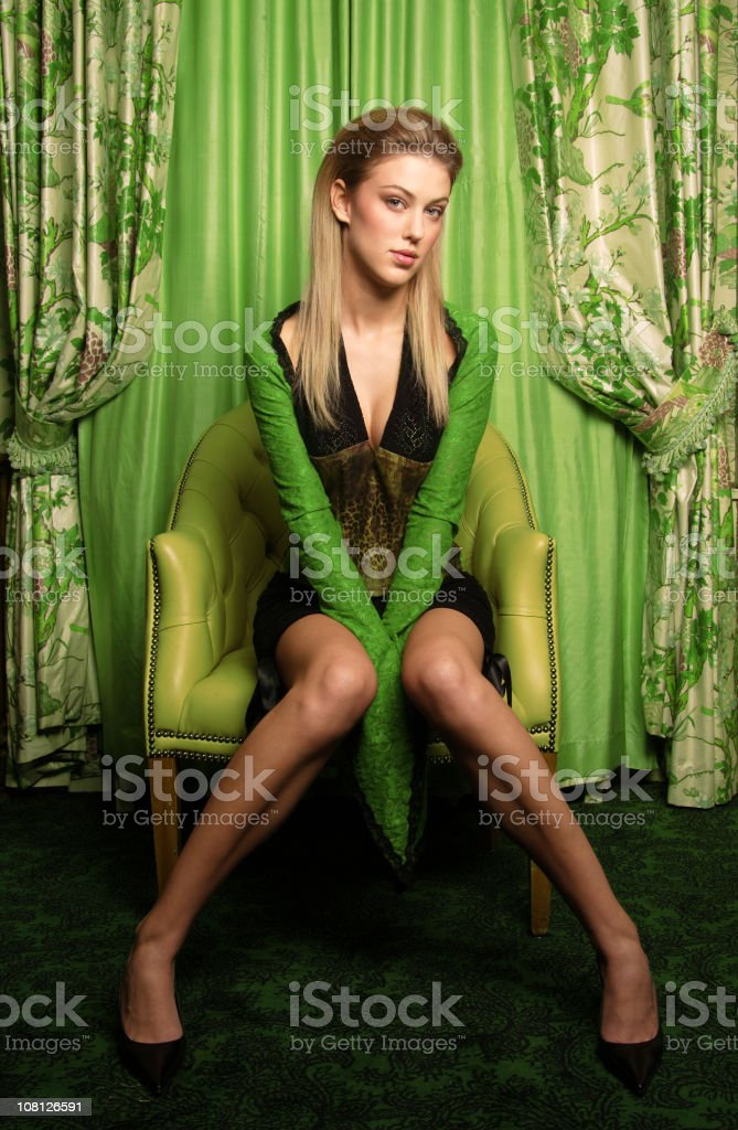 Young Woman Posing on Chair in Elegant Room royalty-free stock photo