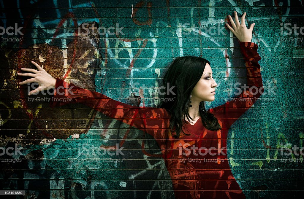 Young Woman Posing on Green Wall with Graffitti Over Top royalty-free stock photo