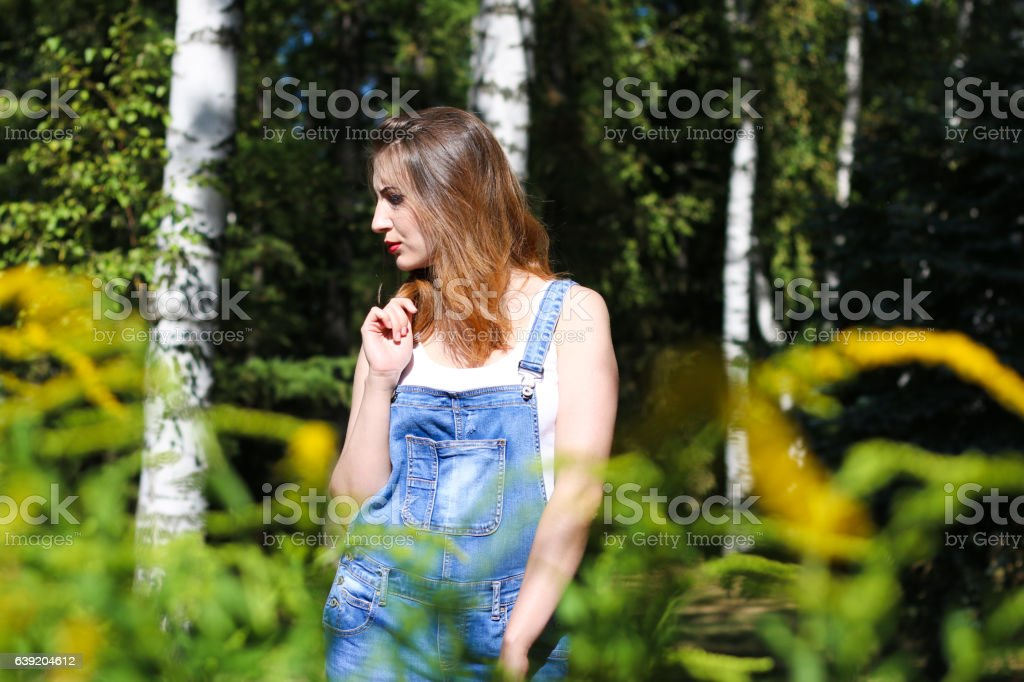 Young woman posing on the background, the foreground bushes stock photo