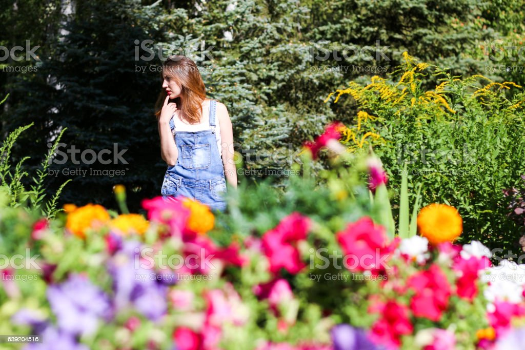 Young woman posing on the background, the foreground flowers stock photo