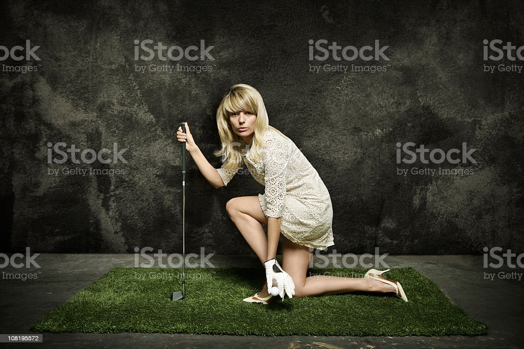 Young Woman Posing on Turf Grass with Golf Club stock photo