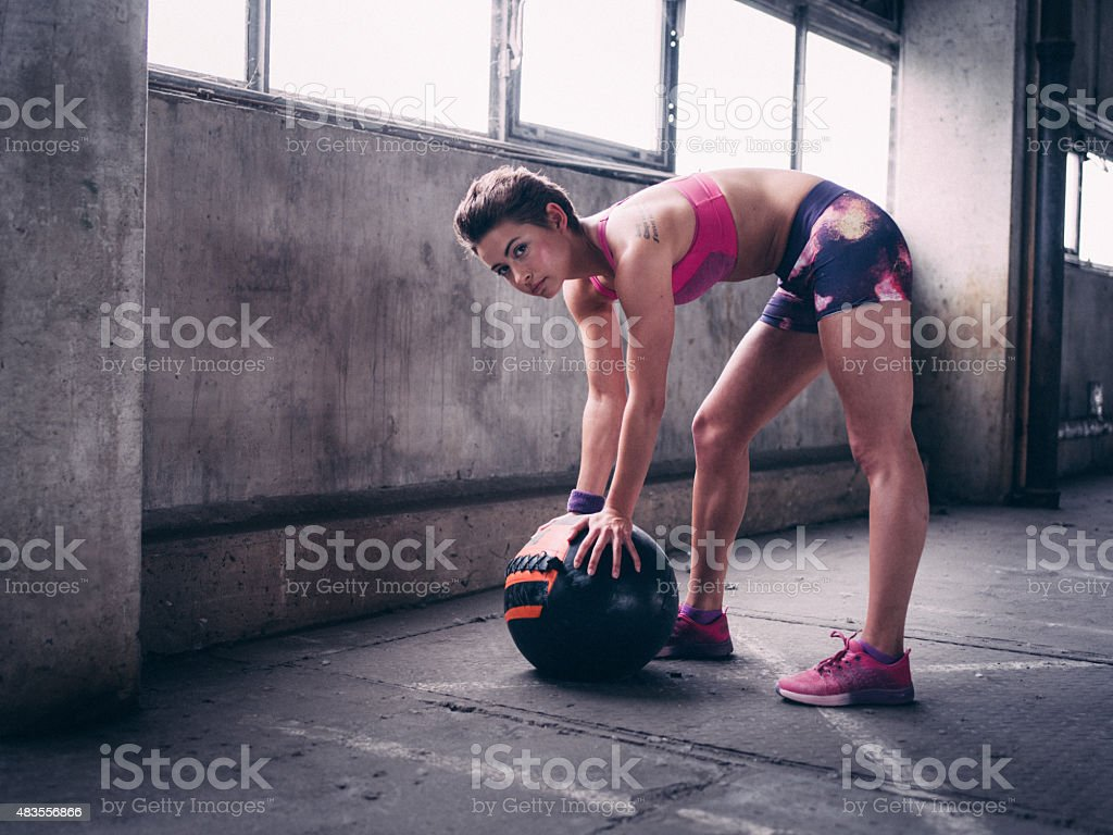 Young woman posing with a medicine ball while gym training stock photo