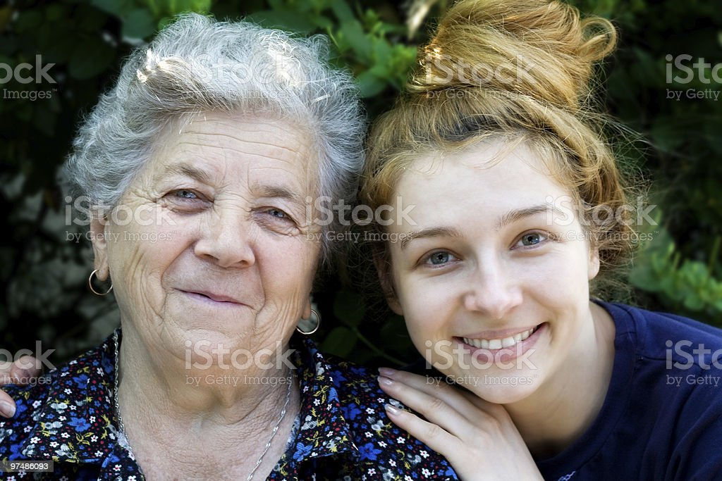 Young woman posing with hands on shoulders of her granny royalty-free stock photo