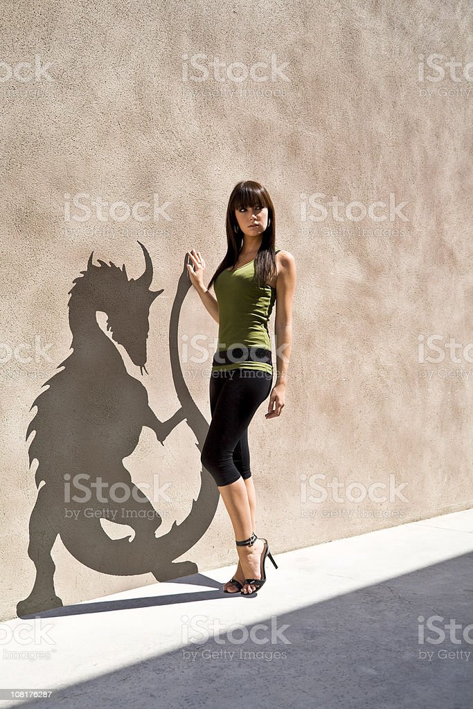 Young Woman Posing with Her Dragon Shaped Shadow on Wall stock photo