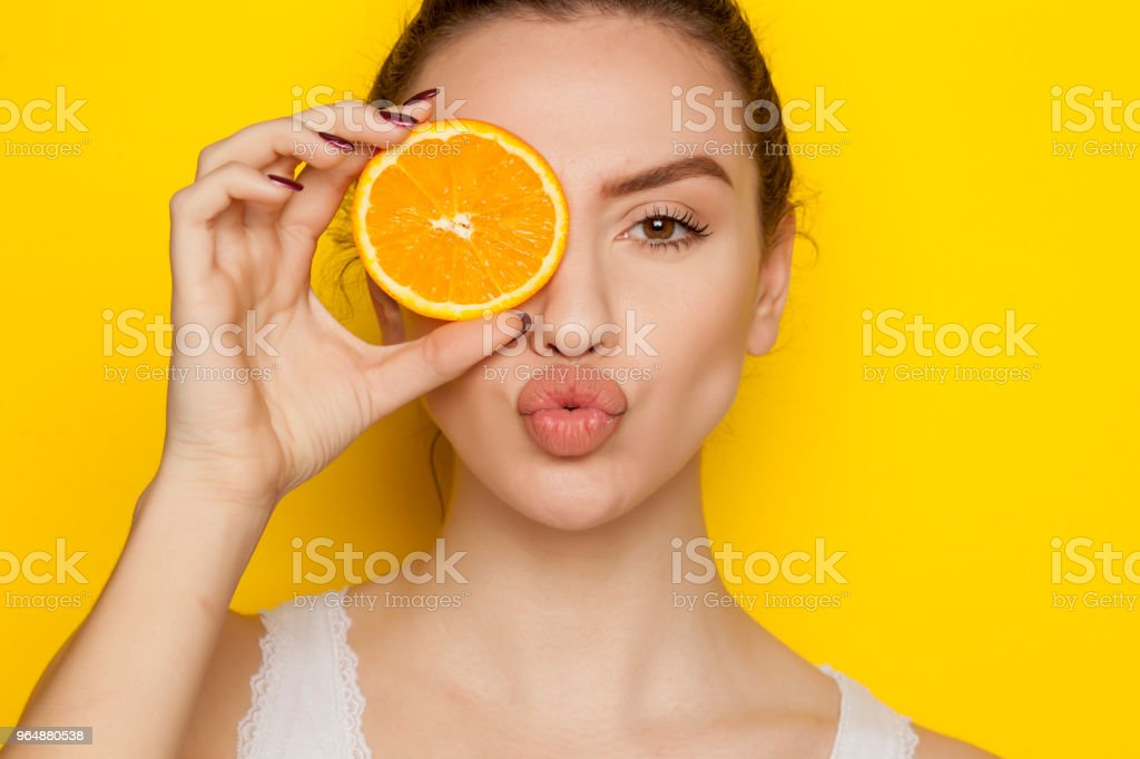 Young woman posing with slice of orange on her face on yellow background royalty-free stock photo
