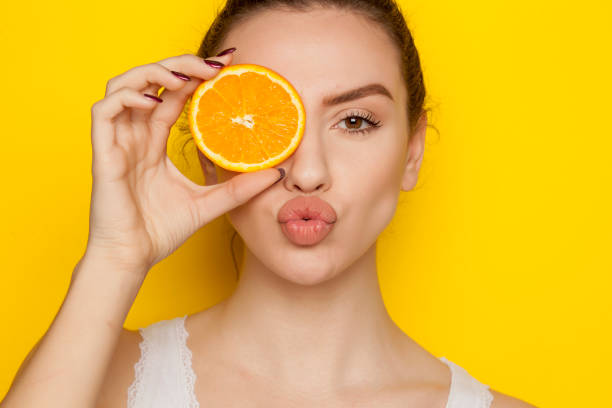Young woman posing with slice of orange on her face on yellow background Young woman posing with slice of orange on her face on yellow background puckering stock pictures, royalty-free photos & images