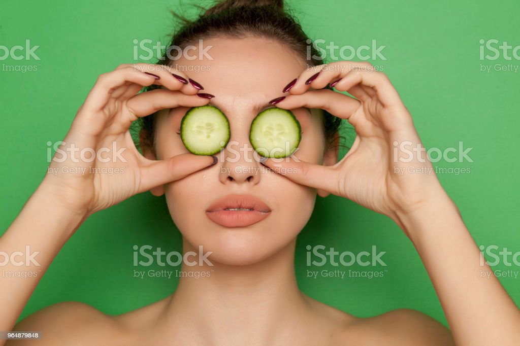 young woman posing with slices of cucumber on her face on green background royalty-free stock photo