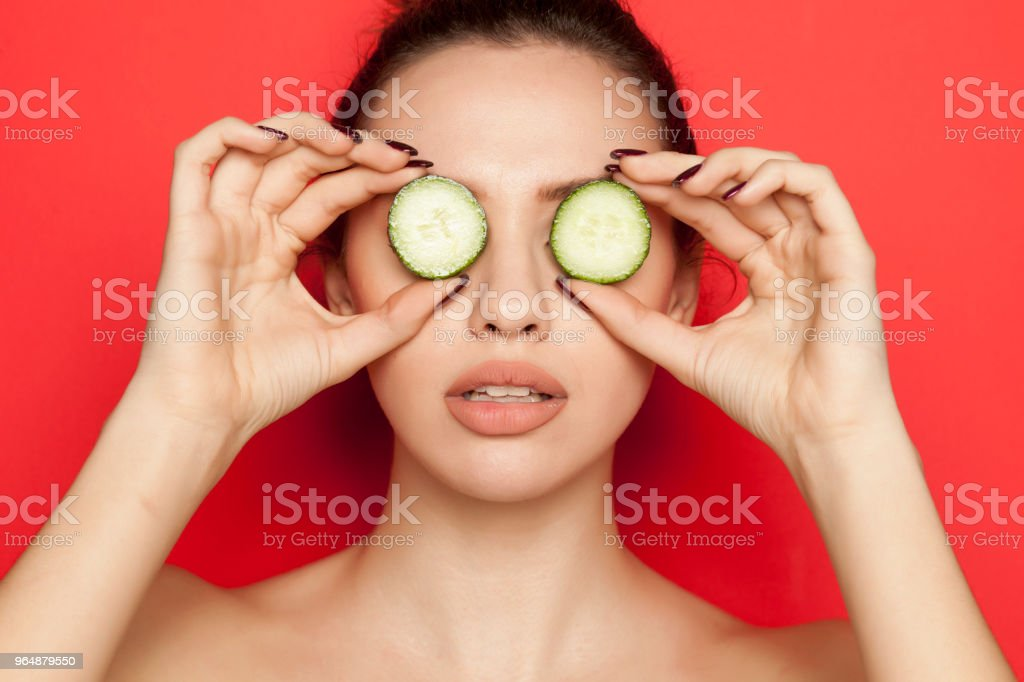Young woman posing with slices of cucumber on her face on red background royalty-free stock photo