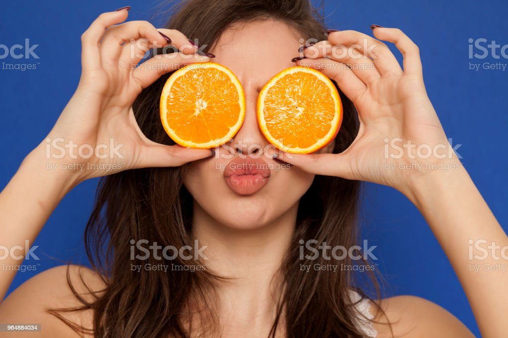 Young woman posing with slices of oranges on her face on blue background royalty-free stock photo