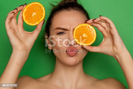 Young Woman Posing With Slices Of Oranges On Her Face On Green Background Stock Photo & More Pictures of Adult