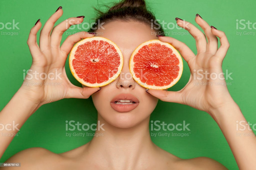 Young woman posing with slices of red grapefruit on her face on green background royalty-free stock photo