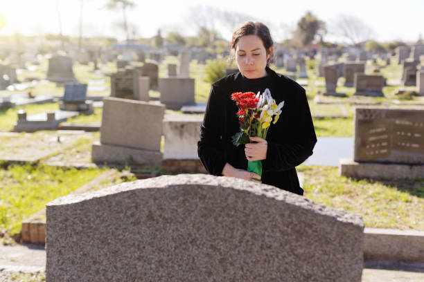 Young woman, possibly a widow, carries flowers to a grave in a cemetery stock photo