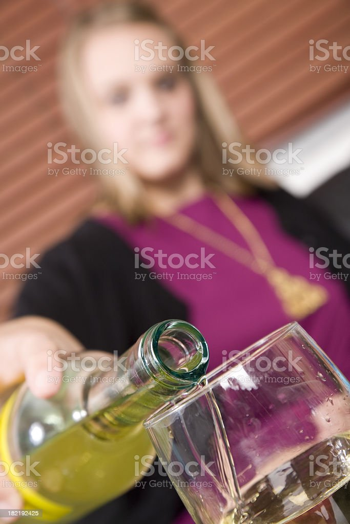 Young Woman Pouring a Drink into Glass royalty-free stock photo