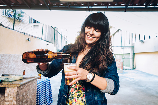 istock Young woman pouring beer on cup 1136351103