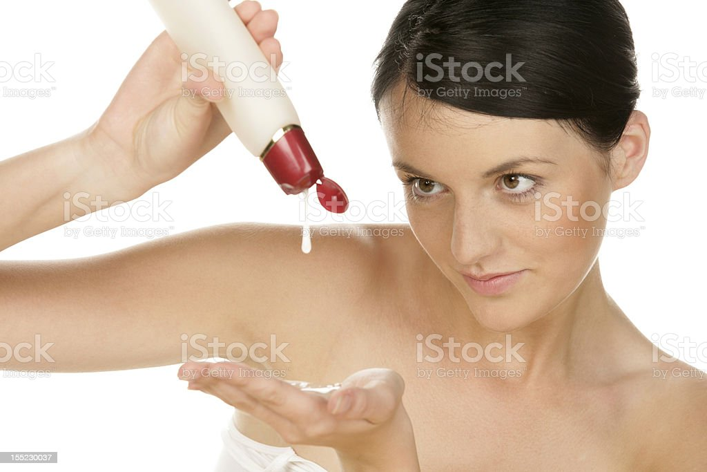 Young woman pouring body lotion into hand royalty-free stock photo