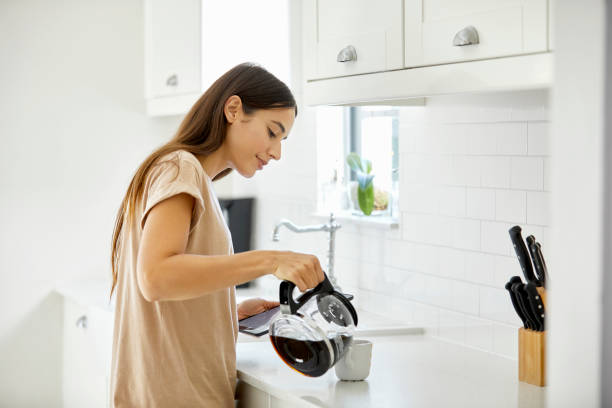 young woman pouring coffee in cup at home - making stock pictures, royalty-free photos & images