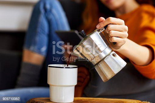 Midsection of young woman holding coffee maker while pouring coffee into cup. Female is having refreshment at home. She is relaxing on chair.