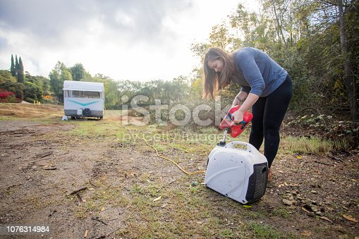 A young woman setting up camp in the wilderness with her trailer