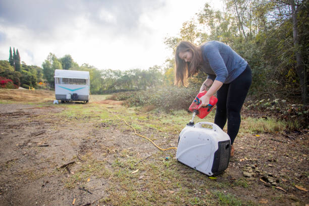 joven mujer vertiendo gas en el generador en el campamento - generadores fotografías e imágenes de stock