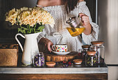 istock Young woman pouring green tea from pot into cup 1182198721