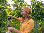 Young woman pouring red wine in glass while in vineyard in Autumn