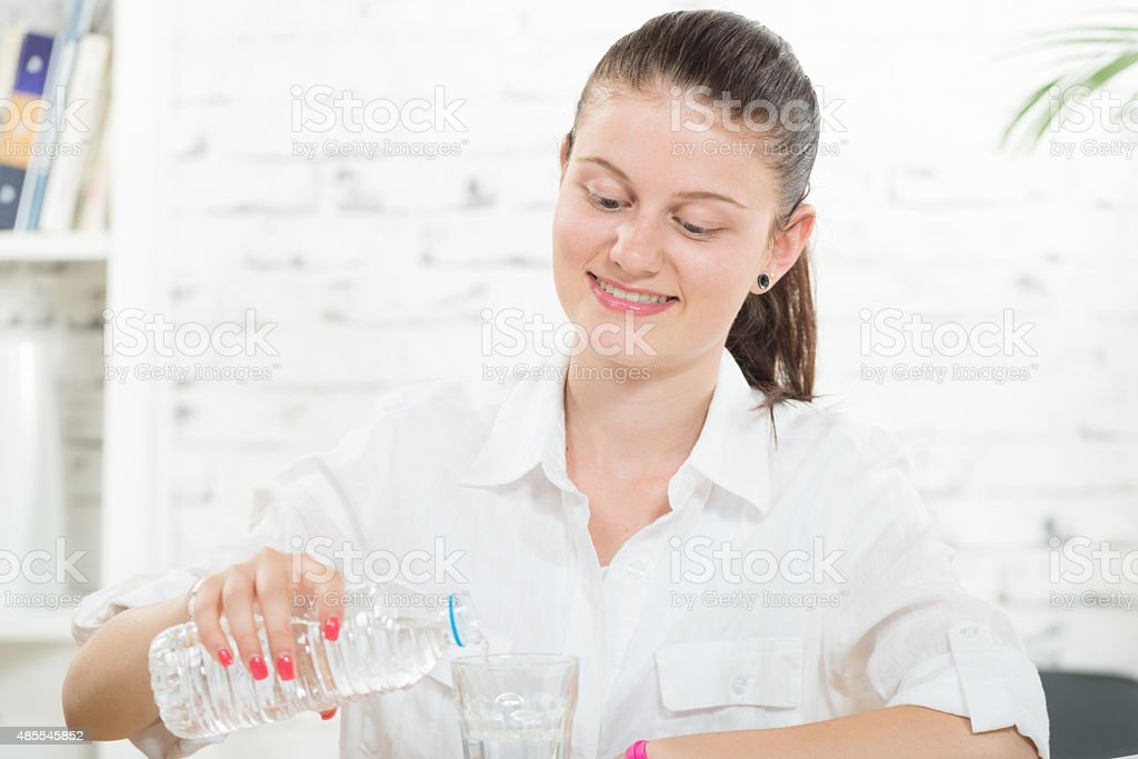 young woman pours a glass of water stock photo