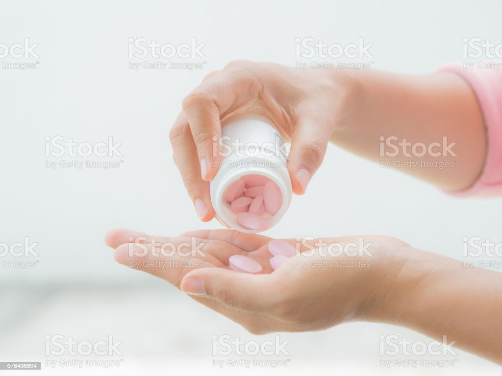 A young woman pours out medicine into her hand royalty-free stock photo