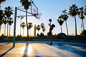 Young woman practicing basketball near the Venice beach in Los Angeles, California. She is having a great time, doing layups.
