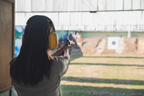 jonge vrouw praktijk pistool schieten op doel - gun shooting stockfoto's en -beelden