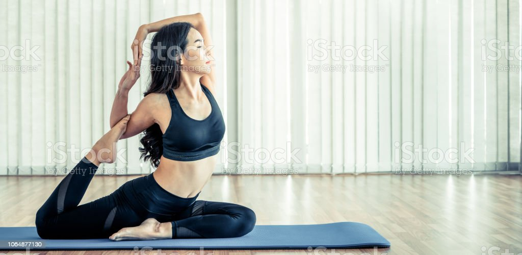 Young woman practicing yoga position in an indoor gym studio. Healthy...