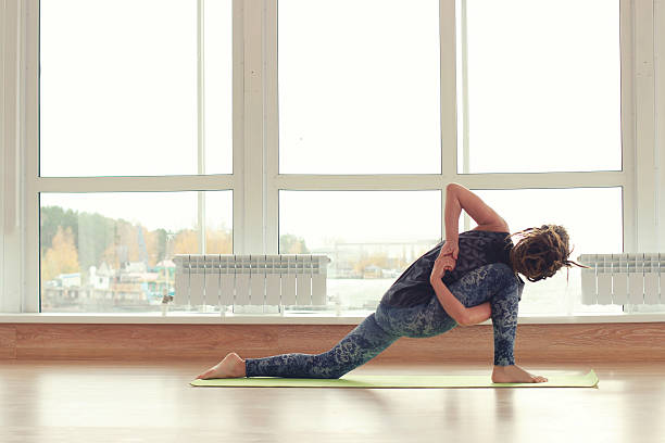 Young woman practice yoga in the bright room. stock photo