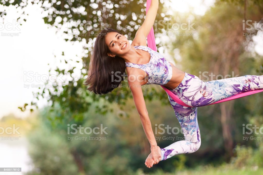 Young woman practices aerial inversion anti-gravity yoga with pink hammock at nature at summer day. Healthy lifestyle and harmony living concept. Freedom, breath and calm stock photo