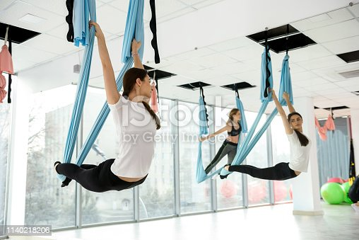 istock Young woman practices aerial yoga in studio 1140218206