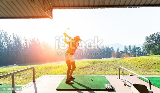 istock Young woman practices her golf swing on driving range, view from behind 1010416102