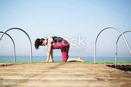 816941230 istock photo Young woman practices yoga on the shore 483375944