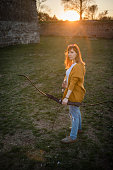 Young Woman practicing Archery on a Meadow in Sunset, Shooting with a Longbow