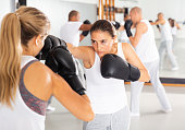istock Young woman practicing boxing punches in sparring 1296106908