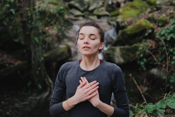 Young woman practicing breathing yoga pranayama outdoors in moss forest on background of waterfall. Unity with nature concept. stock photo